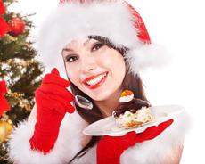 Christmas girl in santa hat eat cake on plate.